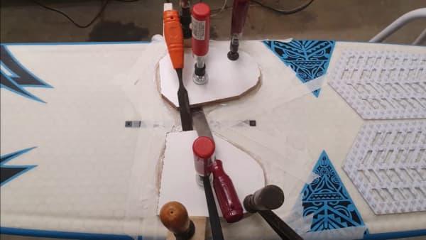 tabla con hydrofoil con varias herramientas para proceder a repararla